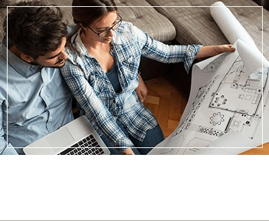 Woman with man beside her looking at house construction plans sitting in couch
